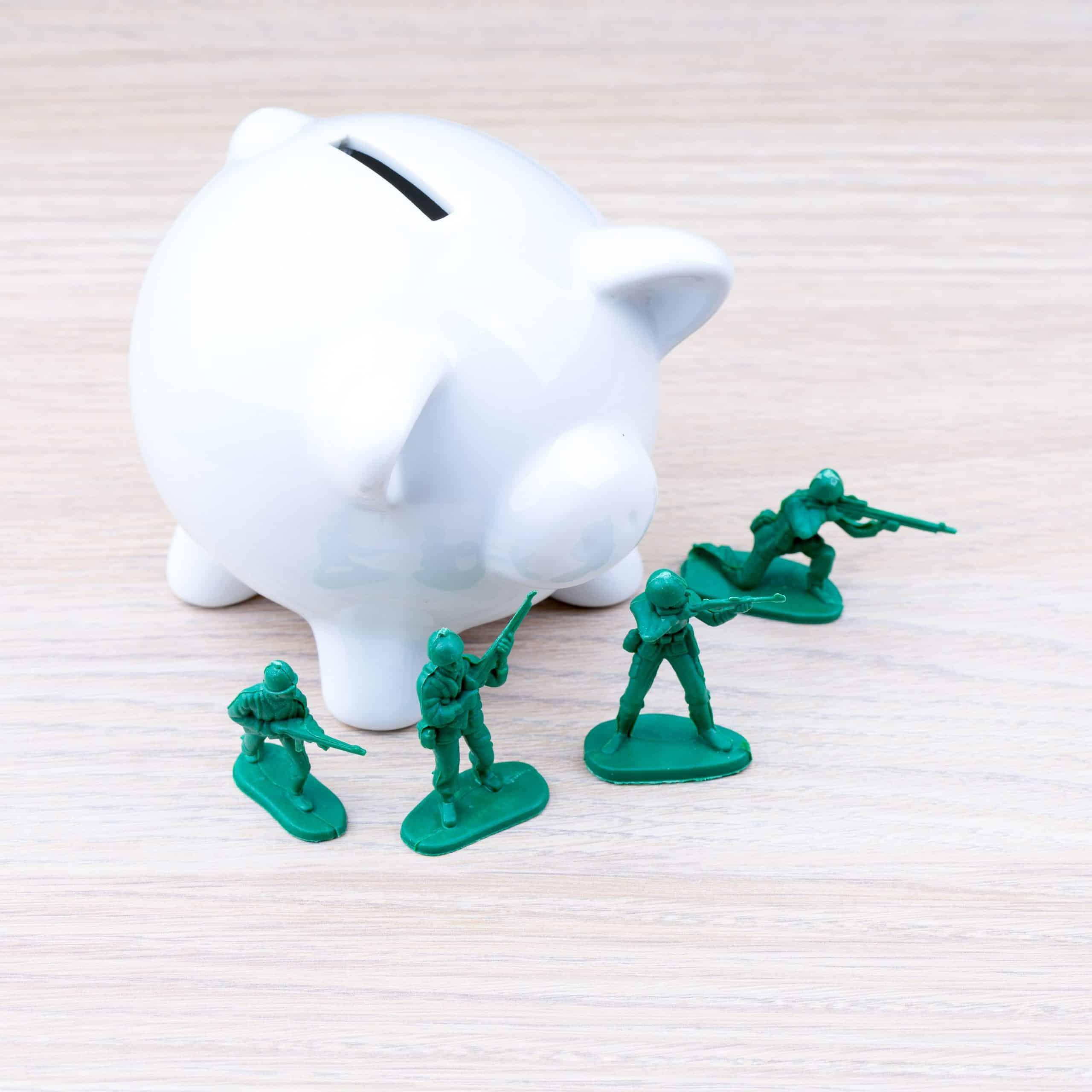 Zöld játék katonák malacpersely előtt, az anyagi biztonság megőrzése vagy befektetés védelme
