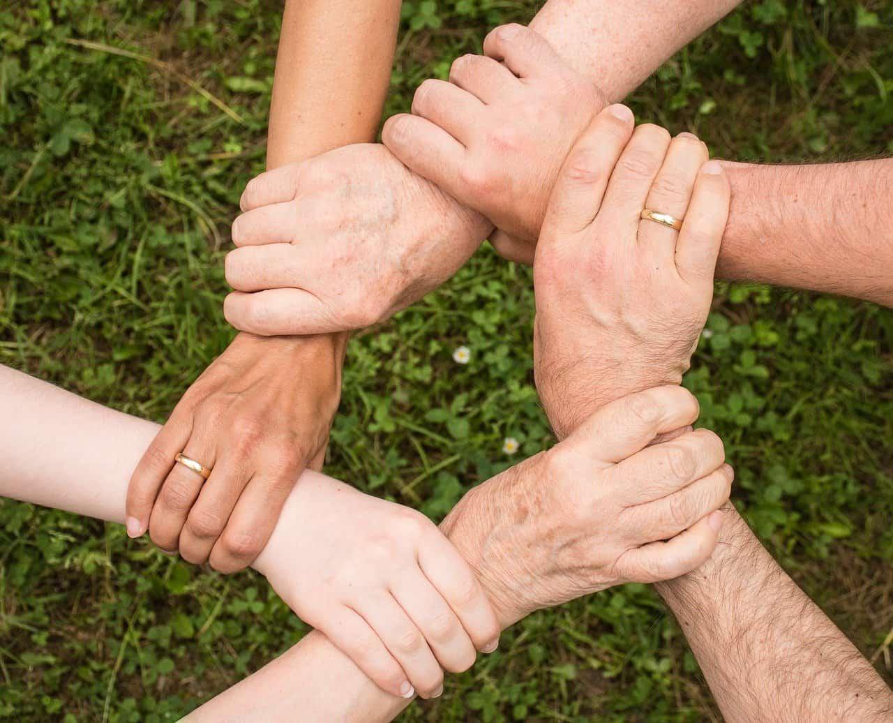 A képen az összefogás szimbólumaként 6 ember fogja egymás kezét